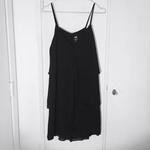 Svart klänning med volang fr H&M. Använd ett fåtal gånger. Fin som den är till fest, eller med t-shirt under till vardags.