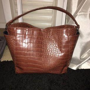 Brun väska från BikBok med fack på sidorna