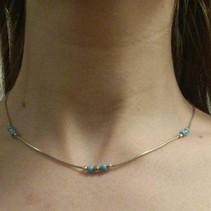 silverhalsband 925S med ljusblåa pärlor. Aldrig använt. Köparen betalar frakten eller möts upp i Stockholm.