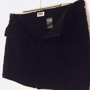 Svart kjol i fleece, värmande med kort och med dragkedja framtill. Fint skick! Köpt på Weekday.