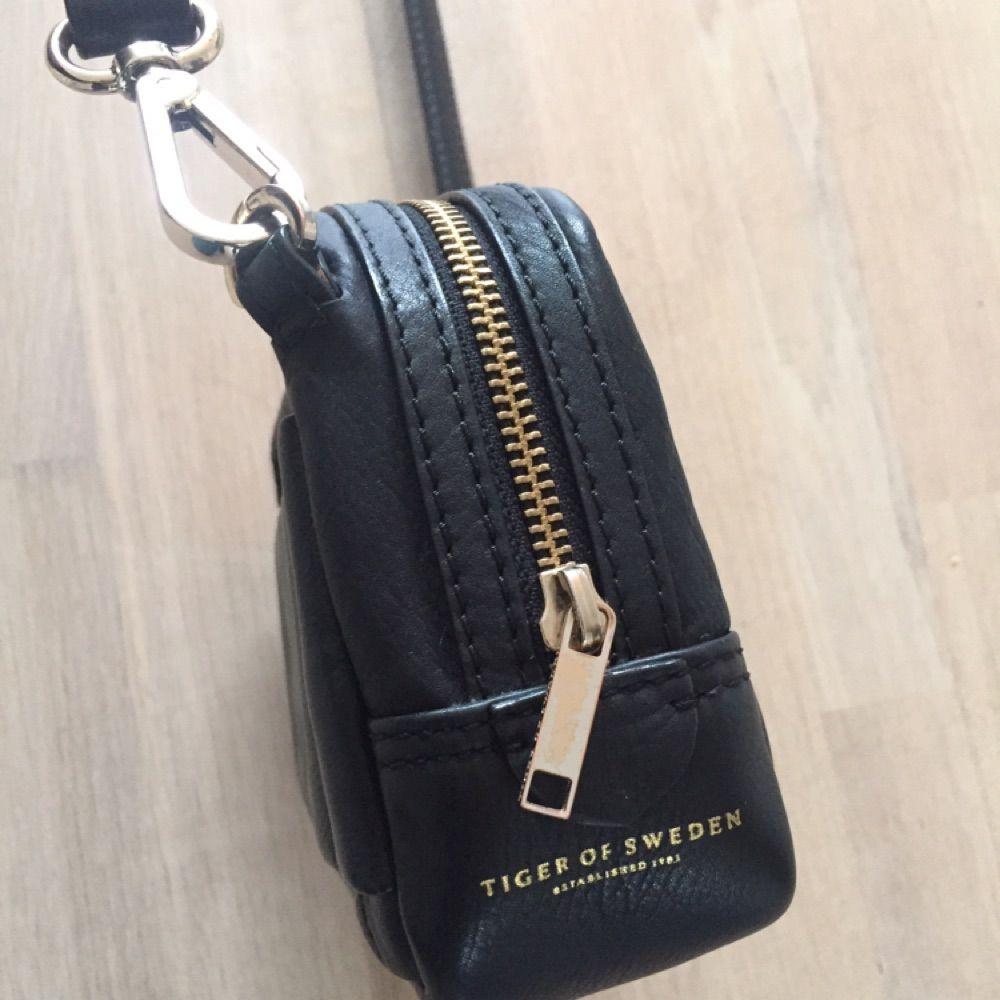 4c7878a9 Tiger-väska i nyskick. Svart skinn med justerbart axelband och detaljer i  guld.