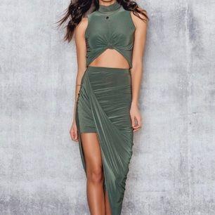 Ett set men en magtröja med hög krage och knut framtill och en kjol med slits. I olivgrön färg. Aldrig använd pga av fel storlek för mig, så den är i gott skick! Märke Club L.