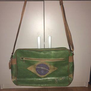 Axelremsväska med Brasiliens flagga endast använd vid två tillfällen, inte smutsig på tredje bilden utan det är väskans design. Äkta läder.