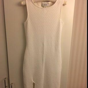 Knälång klänning från Monki med hög slits. Tight passform.