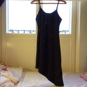 Svart enkel och elegant klänning med smalt silver mönster på. Oanvänd och passar strl XS/S/M. En liten rosett längst upp på framsidan
