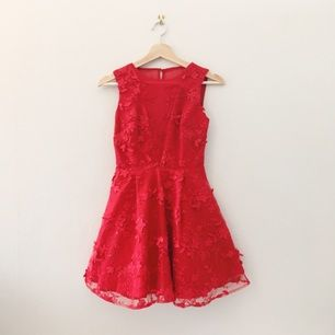 Kort, röd klänning med tyllkjol och vackra blomdetaljer från Chi Chi London. Öppen rygg/mesh med två knappar och dold dragkedja baktill. Nypris 900 kr. Storlek UK 8 Petite. Midjemått ca 65 cm, längd 80 cm.
