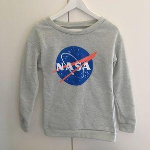 Tröja med NASA motiv. Fleece-material på insidan. Köparen står för frakt.