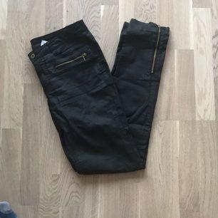 Svarta vaxade byxor med lite glans. Guldiga dragkedjor vid fram-fickan och vid anklarna.
