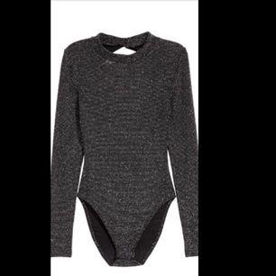 GLITTRIG body i svart och silver. Endast använd en gång på en nyårsfest! Supersnygg med halvpolo och öppen rygg. Fin både under jeans och kjol.  🌹🌹
