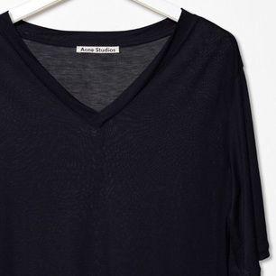 Jättefin T-shirt från Acne Studios, modell Behati Tencel i mörkt marinblå. Lång, oversize och med något längre ärmar. V-ringning. Världens skönaste material. Storlek M - passar även XS och S beroende på hur du vill att den ska sitta. Superfint skick. Nypris runt 900kr. På andra bilden syns passformen bäst, men den är alltså marinblå som i bild 1.