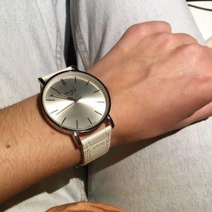 Fin vit och silvrig klocka från märket Regal! Fint skick med justerbart band. Krokodilprint på bandet. Kan fraktas!