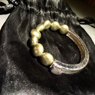 Jättefint tvåsidigt armband från SNÖ of Sweden. Hälften silvrig, hälften gröna pärlor. Påsen medföljer! Silverdelen är något sprucken vilket dock skapat ett fint mönster! Resår i pärldelen så det passar alla.