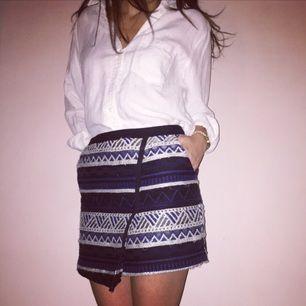 Kjol i omlottmodell med snyggt etno-mönster som går i blått, svart och vitt.