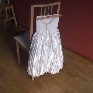 Vit klänning med ballongkjol i siden och vit mudd över bysten. Använd endast en gång och i mycket fint skick. Passar bra som studentklänning!