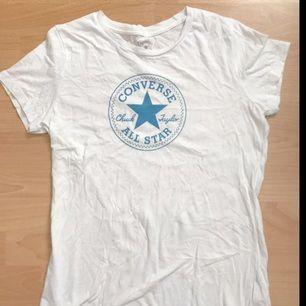 Vit T-shirt med blått converse-tryck. Frakt tillkommer.