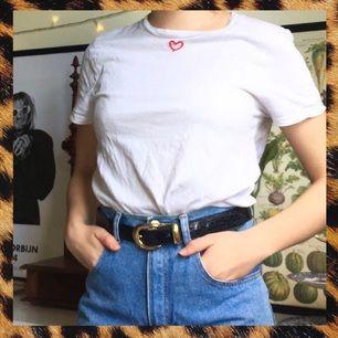 Assnygg vit t-shirt med ett litet rött hjärta påbroderat av mig <3 Supersupersnygg instoppad i ett par jeans eller men ett (kanske rött?!!) linne över!!