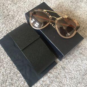 PRADA solglasögon i perfekt skick, endast använda ett fåtal gånger. Inga repor eller dyl. Kommer med samtliga tillbehör (box, fodral, putsduk, certifikat).