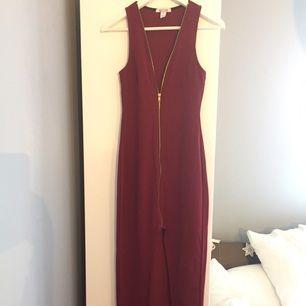 Snygg röd klänning från Nelly, helt oanvänd pga för liten storlek. Det är svårt att få med på bild, men den går ner till anklarna på mig som är 165 cm.  Går att öppna helt med dragkedjan.