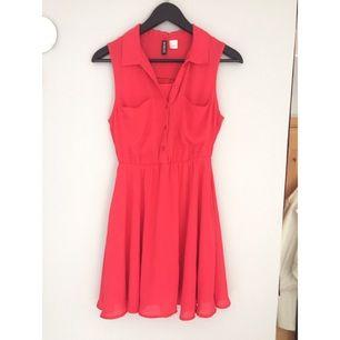Hallon röd/rosa klänning från H&M Divided i storlek 34. I fint skick, med två bröstfickor.