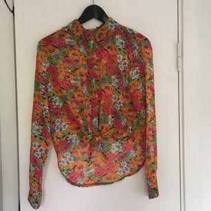 Blommig halvtransparent-skjorta från Boohoo! Oanvänd! Bra skick! Crop-top liknande där fram! Köparen står för frakten! Betalningen sker via swish!
