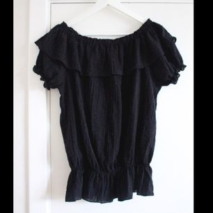 Snygg svart blus med volanger och fina detaljer från Lise Sandahl. Helt oanvänd! Säljer även en likadan i vitt.