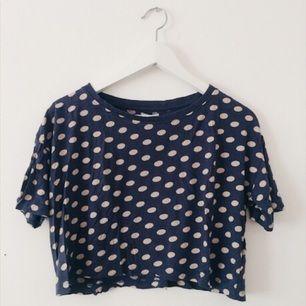 Kortare T-shirt med blå bakgrund och gräddvita prickar