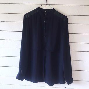 Marinblå skjorta med skinn-detaljer på axlarna