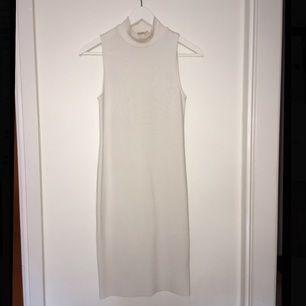 Vit ribbad figursydd klänning i stretchigt material, den slutar precis över knäskålarna på mig som är 1,64! :)
