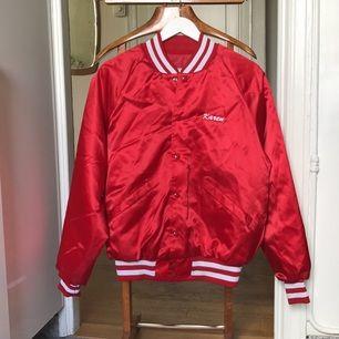 Röd glansig baseball jacka. Second hand i storlek M (passar även storlek S och blir då lite mer baggy modell).