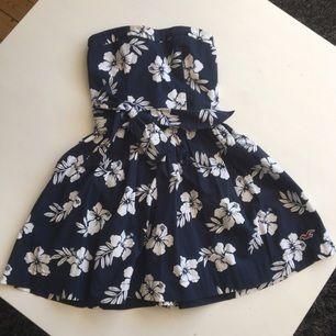 Axelbandslös mörkblå klänning med vita blommor och knyte i midjan!