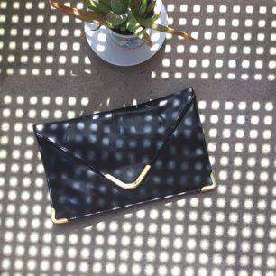 Skitsnygg svart clutch med guldetaljer.