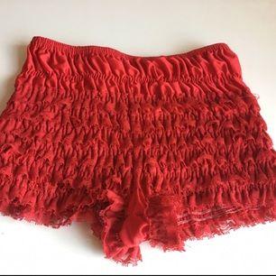 Röda underbyxor (hotpants) med volanger.