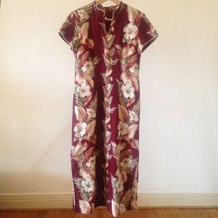 En Kina-Hawaii-klänning! Hellång klänning i Hawaii-mönster.  Axelvaddar, kinakrage och slitsar i sidorna.  Troligtvis bomull.  Ger en riktig timglasfigur.