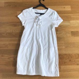 Nästintill oanvänd t-shirt klänning med snörning och fickor. Passar till folk som har storlek S också