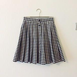 60-tal kjol med hög midja och knappar längst hela framsidan. Utsvängd nertill. Originalknappar (se bild 2) två översta är ditsydda senare och lätta att byta ut. Vintage, köpt i London.