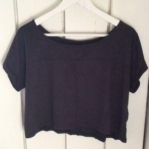 Kort mörk grå t-shirt i oversize storlek. Framsidan av tröjan är i mocka imitation och baksidan i ett bomullsliknande material.