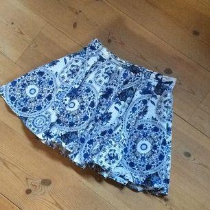 Söt volangkjol i blåa och vita toner med resor baktill så man enkelt kan komma i och ur kjolen. Använd ett fåtal gånger.