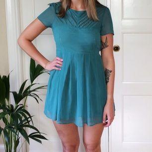 Superfin klänning i blågrönt. Köpte den trots att den var för liten på mig eftersom jag tyckte om den så mycket, så den är knappt använd! Min syster som är modell på bilden är 178 cm så den är lite kort på henne. Frakt tillkommer.