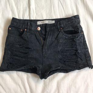 Svarta slitna jeansshorts.