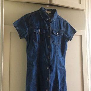 Supersöt avklippt jeansklänning med knappar hela vägen ned och upp. Barnstorlek 164 så passar en XS💕 Köparen står för frakt eller möts upp i Stockholm!