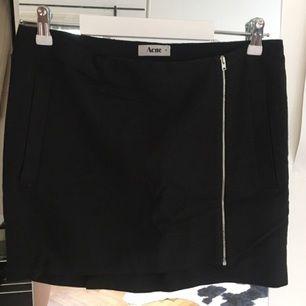 Superfin kort kjol från Acne. Storlek 38 som fungerar till storlek 36/38 beroende på hur högt du vill att den sitter i midjan. Tunn silverdragkedja framtill. Jättefint skick!