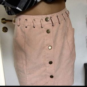 Ljusrosa kjol i fejkmocka! Brons/guldig knäppning fram och knytdetaljer vid midjan fram. Den är uppsydd och något insydd men fortfarande stl 36 och för stor för mig. Omsyningen går att sprätta. Kan fraktas då köparen står för kostnaden!