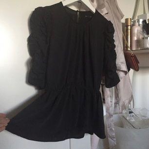Svart blus med fina detaljer och öppning i ryggen
