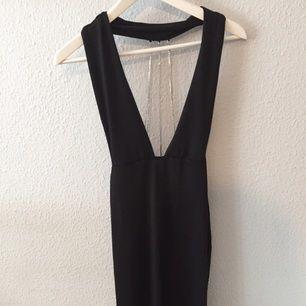 Svart lång klänning med urringning framtill, djup rygg och jättefina detaljer i rygg. Passar S-L då den är väldigt strechig.
