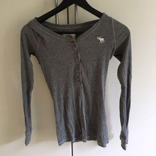 Grå tröja från Abercrombie & Fitch. Köptes för 2/3 år sedan och knappt använd, väldigt fint skick. Säljer pga att ja inte använder den längre. Väldigt skönt material. Frakt ingår i priset