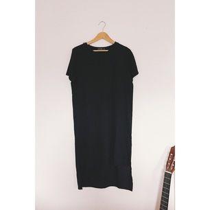 Svart klänning i fint material. Längre tyg över rumpan och kortare framtill. Fint skick!