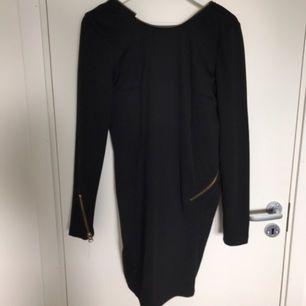 Cool svart klänning med dragkedja runt hals och rygg. Djup i ryggen vilket ger den perfekta party-looken. Fin till både nyår, fest och vardag. Köparen står för frakten :)