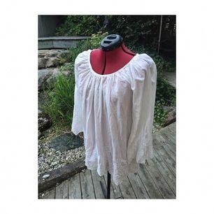 Klänning/tunika i vitt med långa vida ärmar. Virkade/broderade detaljer längst ut på ärmarna och längs med klänningens kant