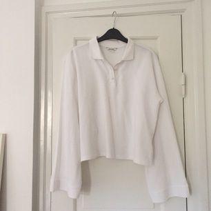 Vit pikéliknande tröja från Monki med vida ärmar. Kortare modell. Använd en gång. Slutsåld i butik.
