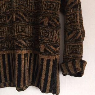 Stickad tröja med ett mönster som ger en spännande vintage känsla som påminner om Egypten. Otroligt charmig.  Har dock ett litet hål uppe i halsen men det går lätt att fixa.